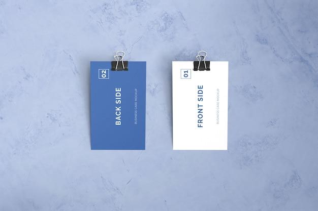 Doppelseitige visitenkarte, die auf marmor mit büroklammermodell legt