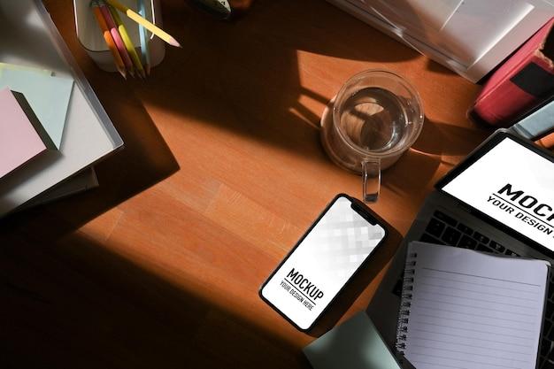 Draufsicht auf arbeitsbereich mit digitalem tablet- und smartphone-modell