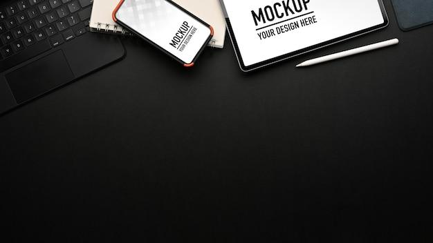 Draufsicht auf arbeitsbereich mit tablet- und smartphone-modell