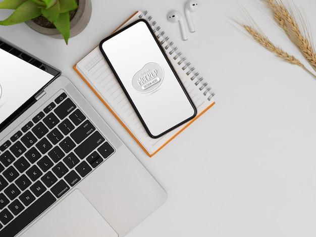 Draufsicht auf modell smartphone, laptop, notebook und kopierraum auf weißem schreibtisch