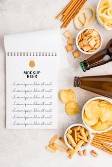 Draufsicht auf notizbuch mit auswahl an snacks und bierflaschen