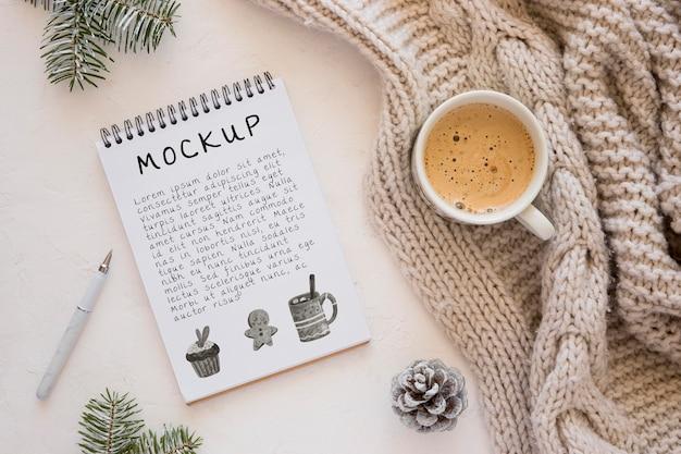 Draufsicht auf notizbuch mit kaffee und pullover