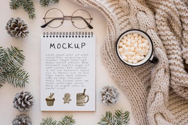 Draufsicht auf notizbuch mit marshmallows und tannenzapfen