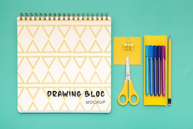 Draufsicht auf schreibtischoberfläche mit notizbuch und schere