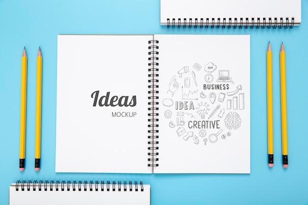 Draufsicht auf schreibtischoberfläche mit notizbüchern und stiften