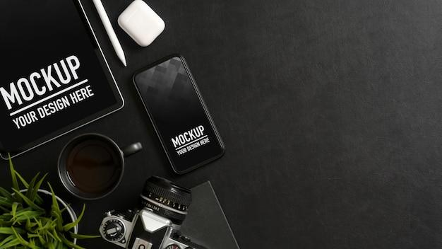 Draufsicht auf schwarzen tisch mit modell smartphone, tablet, zubehör, zubehör und kopierraum