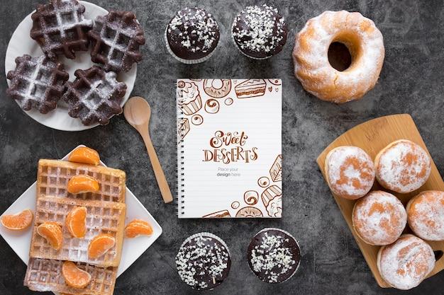 Draufsicht auf sortiment von desserts mit obst und notizbuch