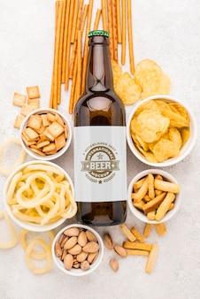 Draufsicht der bierflasche mit einer auswahl an snacks
