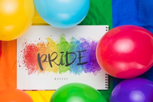 Draufsicht der bunten luftballons mit regenbogen und notizbuch