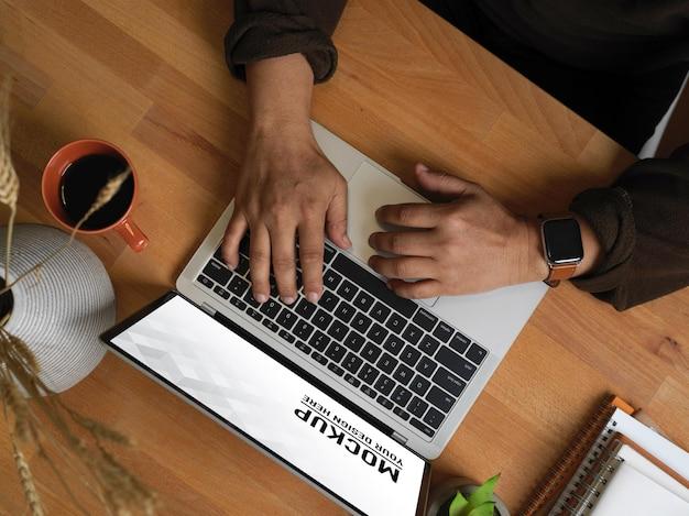 Draufsicht der männlichen hände, die auf laptop-modell tippen