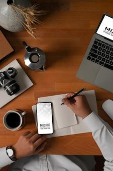 Draufsicht der männlichen hand, die mit notebook- und smartphone-modell arbeitet