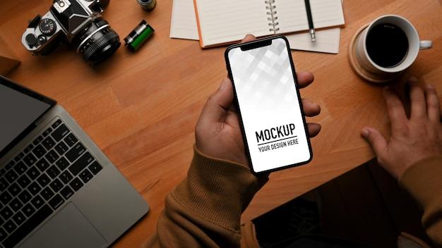 Draufsicht der männlichen hand, die smartphone-modell auf arbeitstisch hält