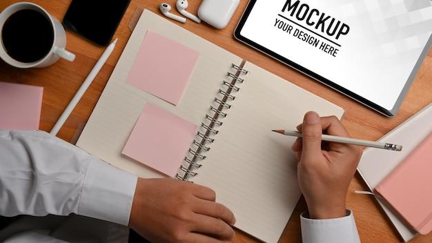 Draufsicht der männlichen hand, die zeitplanbuch und kaffeetasse mit tablettenmodell hält