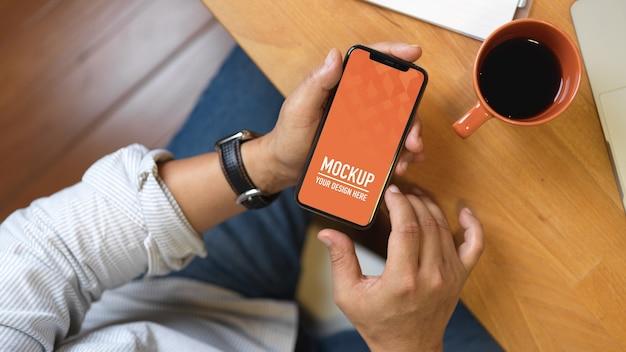 Draufsicht der männlichen hand unter verwendung des smartphone-modells