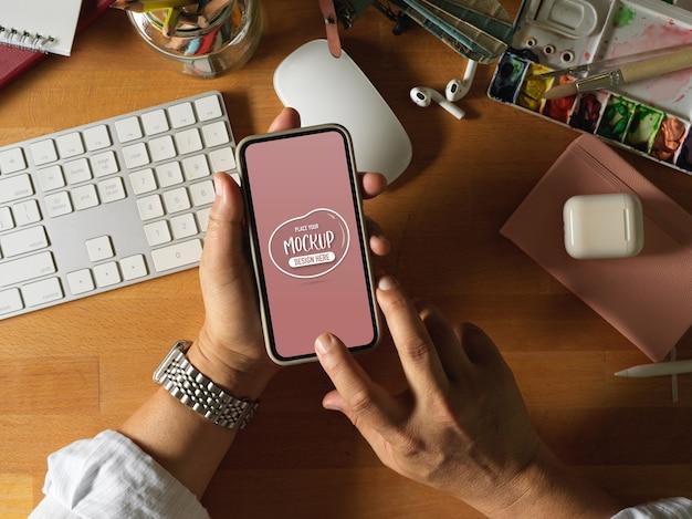 Draufsicht der männlichen künstlerhände unter verwendung des modell-smartphones auf hölzernem arbeitstisch mit malwerkzeugen