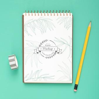 Draufsicht der schreibtischoberfläche mit notizbuch und bleistift