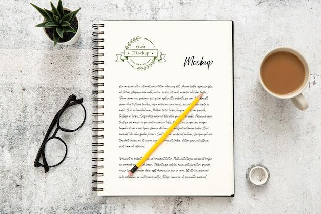 Draufsicht der schreibtischoberfläche mit notizbuch und kaffee