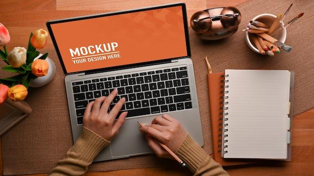 Draufsicht der weiblichen hände, die auf laptop-modell auf dem tisch mit notizbuch tippen