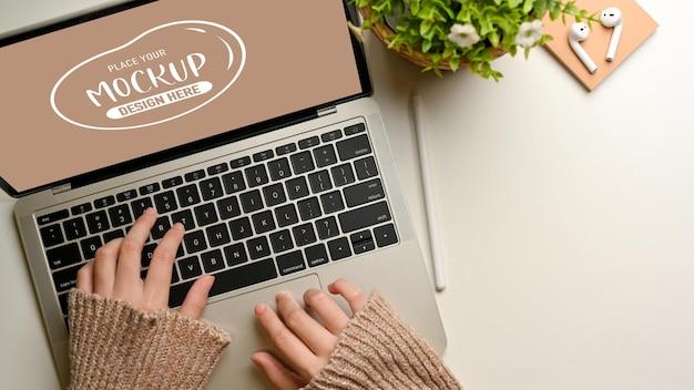 Draufsicht der weiblichen hände, die auf laptop-modell auf weißem tisch tippen, der mit blumentopf verziert wird