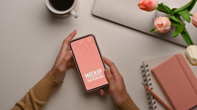 Draufsicht der weiblichen hände, die smartphone-modell auf weiblichem arbeitsbereich halten