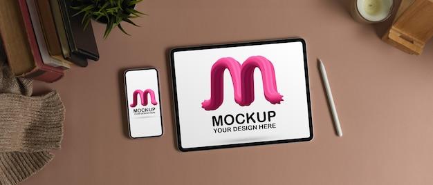 Draufsicht des arbeitsbereichs mit digitalem tablet, smartphone, büchern und dekorationen des modells auf rosa tisch