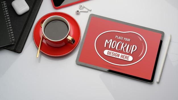 Draufsicht des arbeitsbereichs mit mock-up-tablette, kaffeetasse und zubehör im büroraum