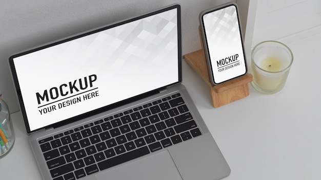Draufsicht des arbeitsbereichs mit modell-laptop und smartphone auf weißem tisch im büroraum