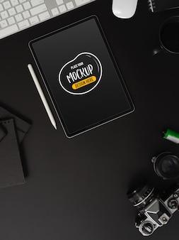 Draufsicht des arbeitstisches mit mock-up-tablette mit stift und büromaterial auf schwarzem tisch