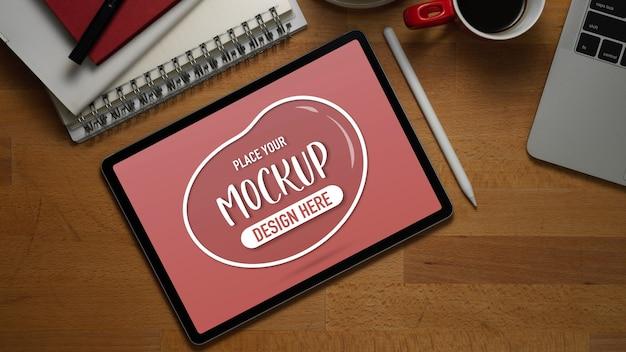 Draufsicht des arbeitstisches mit modell digitalem tablet, laptop, verbrauchsmaterial und kaffeetasse im heimbüro