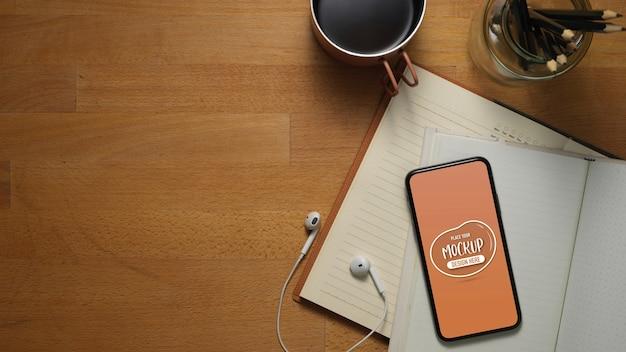 Draufsicht des arbeitstisches mit modell-smartphone auf geöffneten notizbüchern, kopfhörern, bechern, stiften