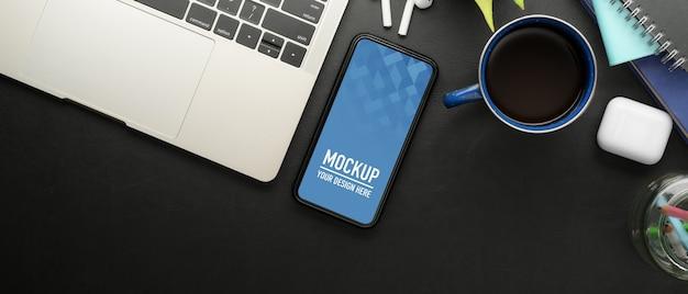 Draufsicht des arbeitstisches mit modell smartphone, laptop und büromaterial im büroraum