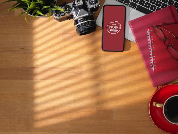 Draufsicht des bequemen arbeitsbereichs mit modell-smartphone, laptop-computer