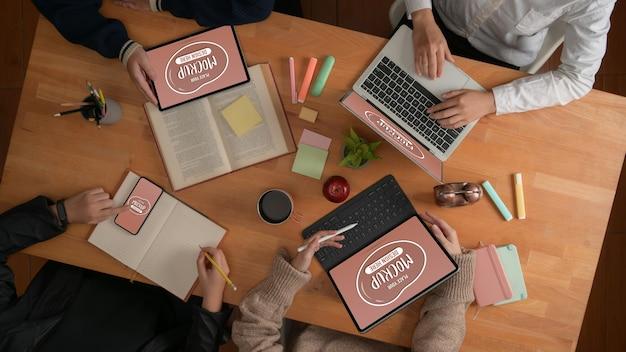 Draufsicht des designerteams, das an ihrem projekt mit modell der digitalen geräte zusammenarbeitet