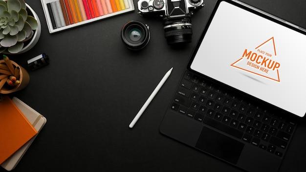 Draufsicht des dunklen arbeitsbereichs mit digitalem tablet-kamera-malwerkzeug-briefpapier