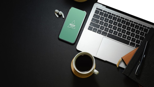 Draufsicht des dunklen arbeitsbereichs mit laptop-modell