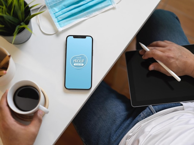 Draufsicht des geschäftsmanns, der am arbeitsplatz sitzt und kaffeetasse und modell-smartphone hält