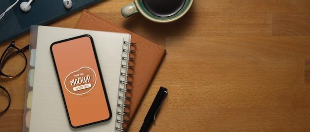 Draufsicht des hölzernen arbeitstisches mit modell-smartphone, briefpapier, zubehör und kopierraum