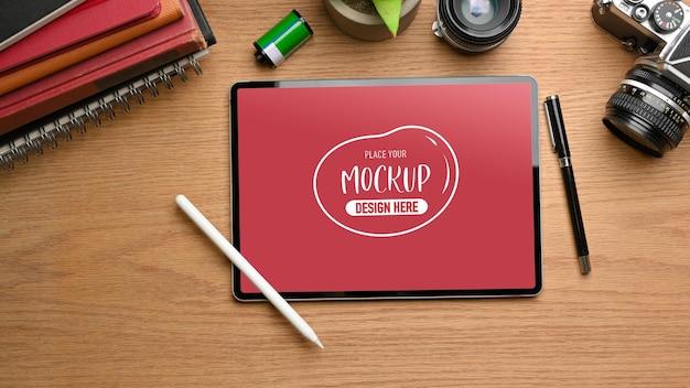 Draufsicht des kreativen flachen laienarbeitsbereichs mit digitalem tablet-modell, kamera, büchern und zubehör