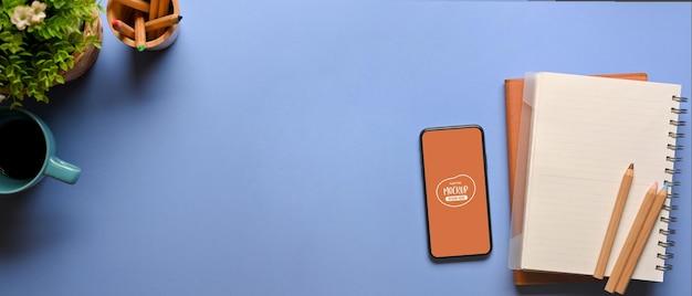 Draufsicht des kreativen flachen laienarbeitsbereichs mit smartphone-schreibwarenbecher-blumentopf