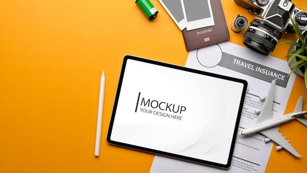 Draufsicht des kreativen flachen laienfotos des gelben tisches mit digitaler tablet-reiseversicherungsformular-passkamera