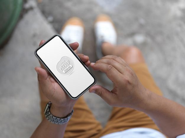 Draufsicht des mannes, der verspottetes smartphone hält, während draußen steht