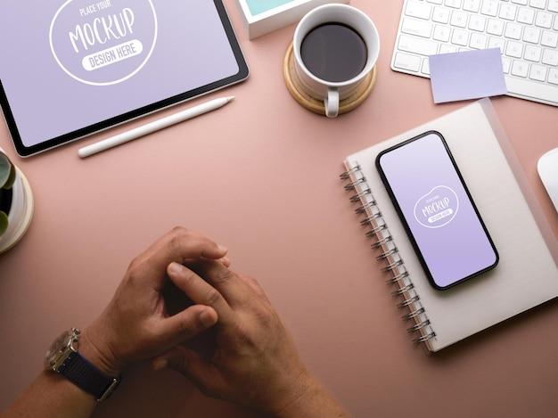 Draufsicht des mannes legen seine hände auf arbeitsbereich mit smartphone-modell