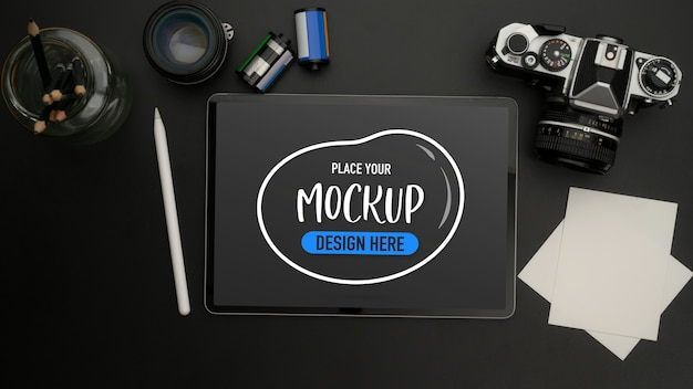 Draufsicht des modell-digitalen tablets auf schwarzem tisch mit kamera, notizblock, objektiv und briefpapier