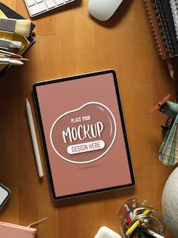 Draufsicht des modell-digitalen tabletts auf holztisch mit vorräten und dekorationen