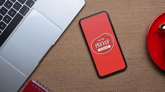 Draufsicht des modell-smartphones auf arbeitsbereich mit laptop, notebook und kaffeetasse