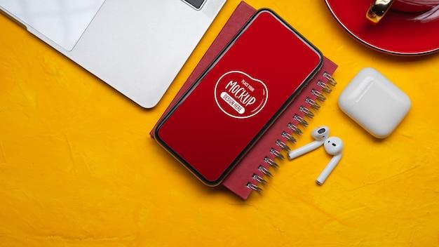 Draufsicht des modell-smartphones auf buntem arbeitsbereich mit laptop und zubehör