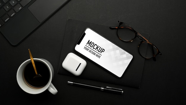Draufsicht des modell-smartphones auf schwarzem tisch mit zubehör