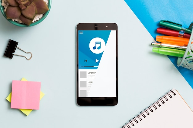 Draufsicht des smartphones mit notizbuch und haftnotizen auf schreibtisch