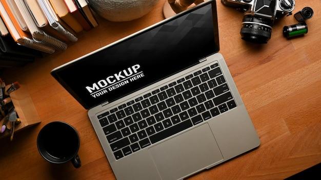 Draufsicht des studientisches mit laptop-modell, büchern, kamera und briefpapier