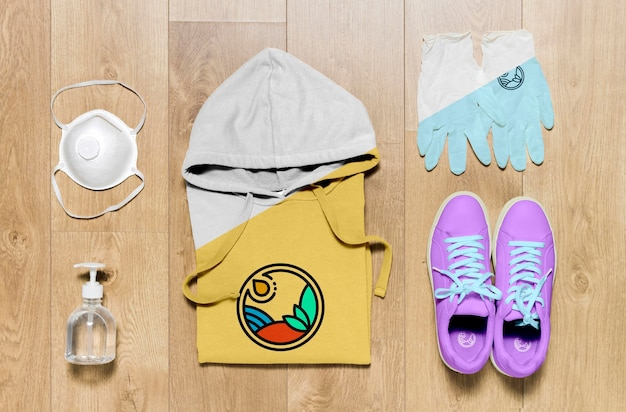 Draufsicht gefaltetes hoodie-modell mit händedesinfektionsmittel, maske und handschuhen